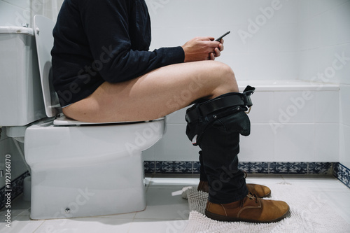 Valokuva  Man in the toilet with smartphone