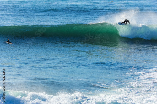 Leinwand Poster Surfer in California surfs large wave in beautiful blue water at beach