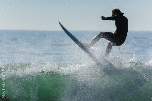 Fotomural Surfer in California surfs large wave in beautiful blue water at beach