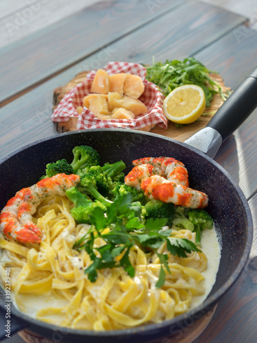 Láminas  Whole grain pasta with shrimps and cheese on wooden table, top view