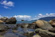 View of Juliao beach in Ilhabela - Sao Paulo, Brazil - with rocks in the sea on sunny day with blue sky with clouds