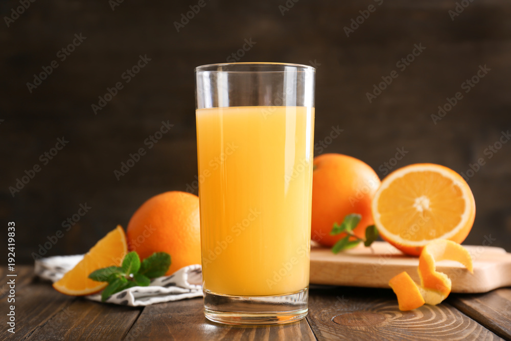 Fototapeta Glass of fresh orange juice on wooden table