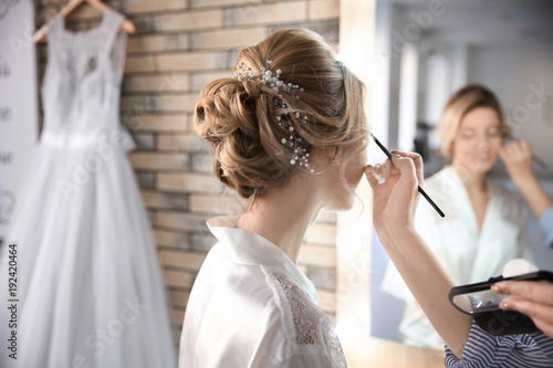 Leinwand Poster Makeup artist preparing bride before her wedding in room