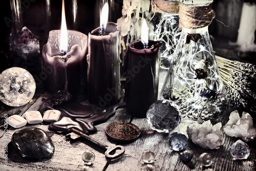 Foto Black candles, crystals and stones, ancient runes, key and ritual bottles on witch table Halloween, occult, esoteric and wicca concept