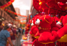 Red Dog Dolls Hanging At Shop During Chinese New Year Festival, China Town, Blurred Local People And Tourists With Lanterns Decoration As Background