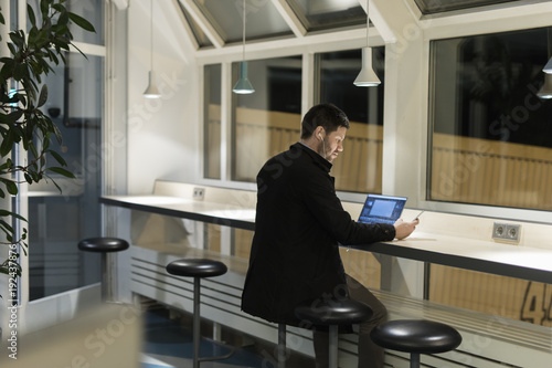 Man with laptop and smart phone at airport in Sweden