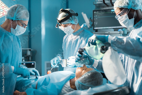 Fotomural  african american anesthetist holding oxygen mask above patient during surgery