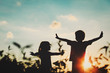 canvas print picture - little boy and girl silhouettes play at sunset