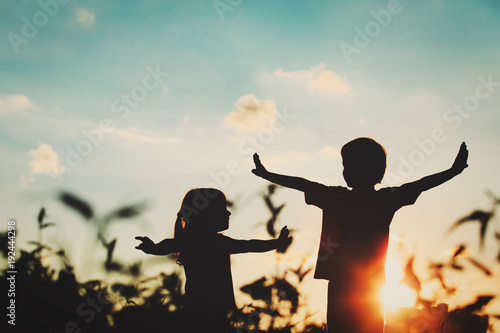 Fotomural little boy and girl silhouettes play at sunset