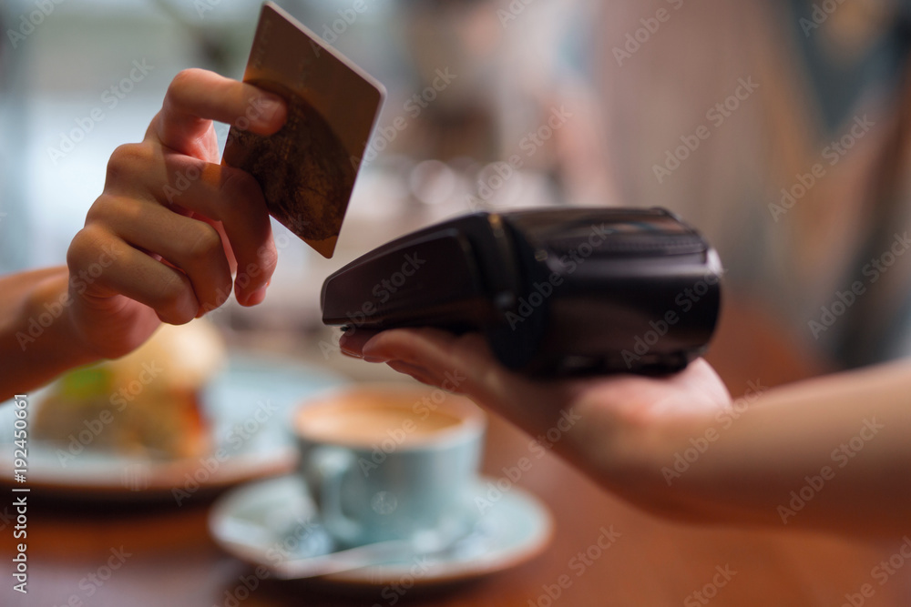 Fototapeta Credit card usage. Moment of payment with a credit card hold by female hand through terminal which carried by another hand