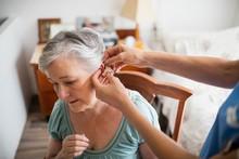 Nurse Putting Hearing Aid To A...