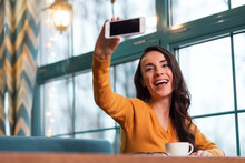 Sincere Selfie. Beautiful Merry Cute Woman Laughing While Elevating Phone And Taking Shot