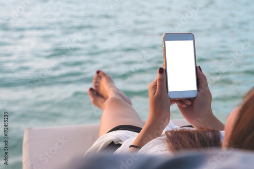 Fotografie, Obraz  Mockup image of a woman using white mobile phone with blank desktop screen while