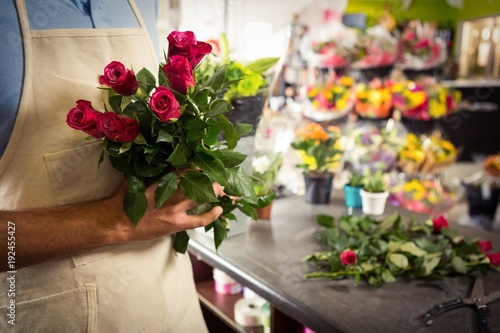 Close-up of florist holding a bunch of rose's in flower shop