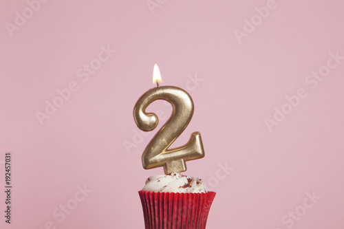 Fotografia Number 2 gold candle in a cupcake against a pastel pink background