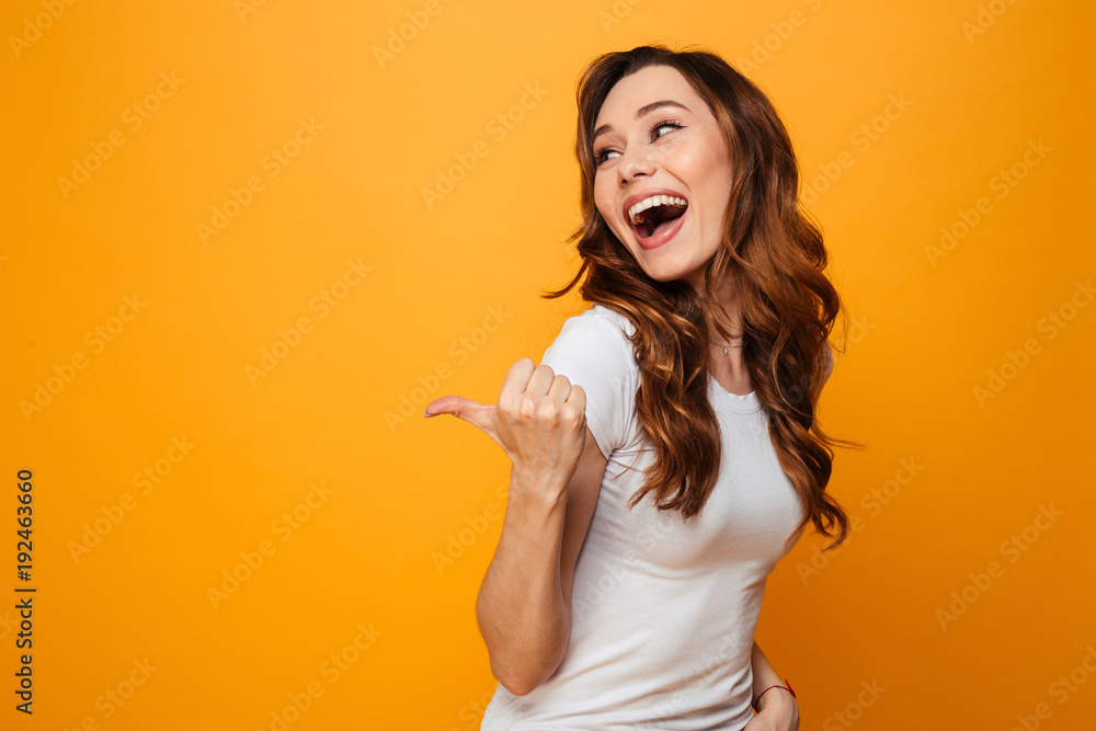 Fototapety, obrazy: Laughing brunette woman in t-shirt looking and pointing away