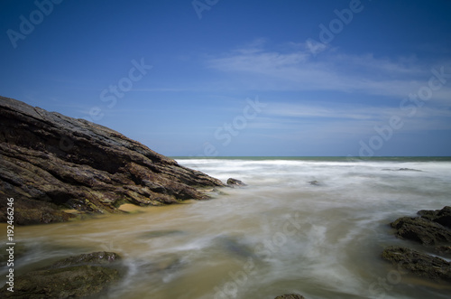Staande foto Tropical strand wild tropical island and rocky sea shore under bright sunny day and blue sky background.
