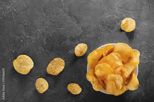 Pile of crispy potato chips lying  on an old concrete table in kitchen. Concept of fast food background. Free place for text, top view.