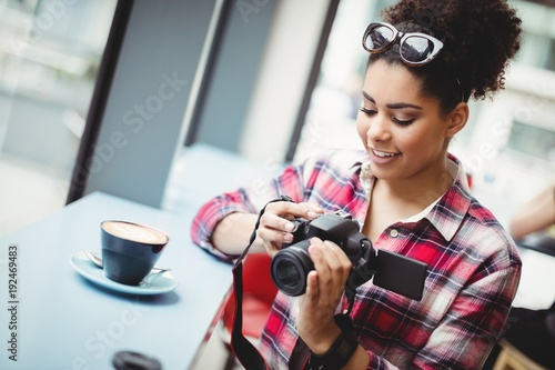 Smiling young woman holding camera at restaurant