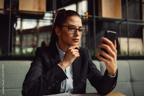 Close-up of young businesswoman in cafeteria looking at screen of her mobile phone Poster