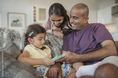 Fotografie, Obraz  Father and Daughters Using a Digital Tablet