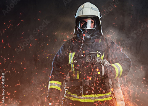 A firefighter dressed in a uniform in a studio. Canvas Print
