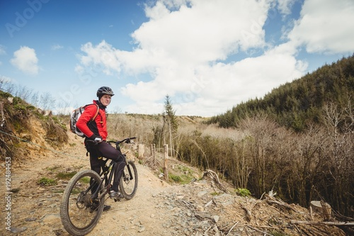 Biker with bicycle passing through mountain trail against sky