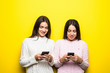 canvas print picture - Photo of two cheerful girls chatting isolated over yellow background.