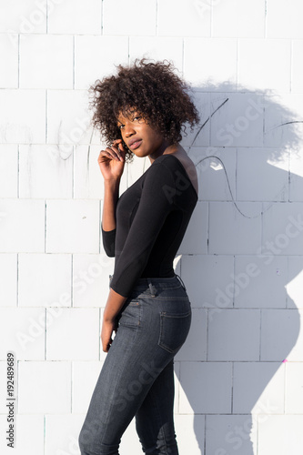 Ethnic woman at white wall