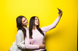 canvas print picture - Portrait of two lovely girls dressed in sweaters standing and taking a selfie isolated over yellow background