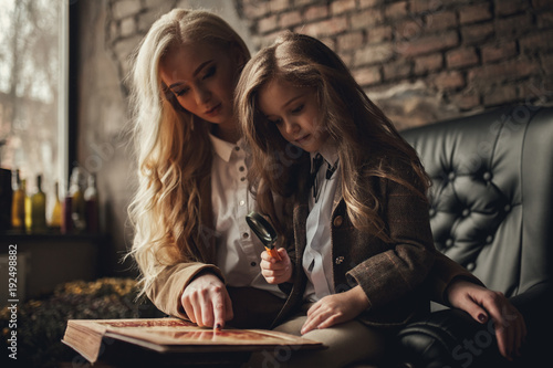 Child girl with woman in image of Sherlock Holmes sits in armchair and looks photoalbum with magnifier on background of old interior Wallpaper Mural