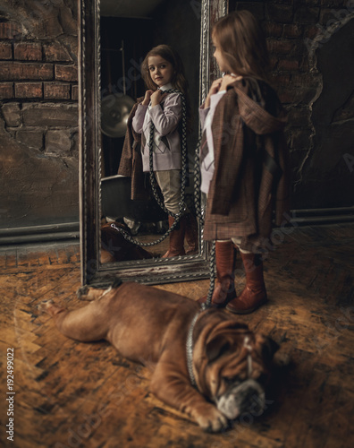 Fotomural Child girl in image of Sherlock Holmes stands next to English bulldog and looks at mirror reflection on background of old interior