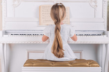 Little Blond Girl Play On White Piano In White Dress