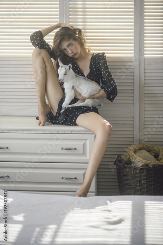 Girl with baby sheep on chest of drawers