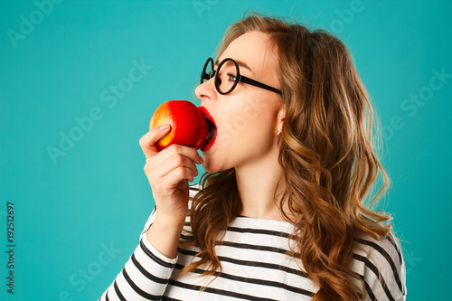 Poster Kruidenierswinkel Portrait of young beautiful blond woman in round black glasses eating red apple over blue background