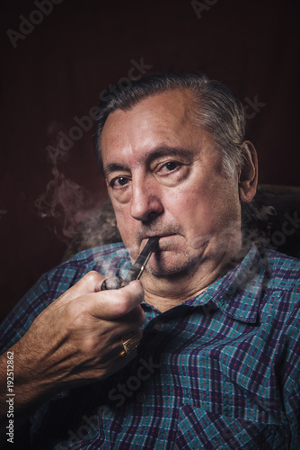 Fotografía  Classy senior elderly man smoking a pipe in his armchair, red background
