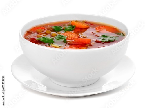 Homemade tomato, lentil soup in a white bowl with saucer. Side view isolated on a white background.