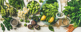 Spring healthy vegan food cooking ingredients. Flat-lay of vegetables, fruit, seeds, sprouts, flowers, greens over white wooden background, top view. Clean eating, diet food concept