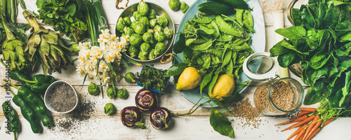 Poster Cuisine Spring healthy vegan food cooking ingredients. Flat-lay of vegetables, fruit, seeds, sprouts, flowers, greens over white wooden background, top view. Clean eating, diet food concept