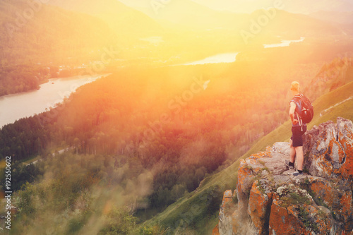 Papiers peints Beige Tourist plaid shirt and with backpack standing on top of mountain and having fun against backdrop of mountains, rivers. setting sun