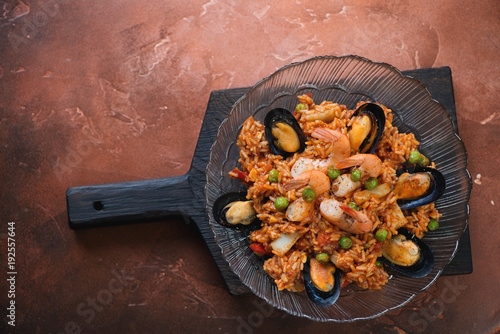 Plate with seafood paella on a black wooden serving board, top view on a fire warm rusty metal background, copyspace