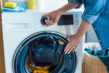 Cropped Shot Of Woman Using Washing Machine At Home
