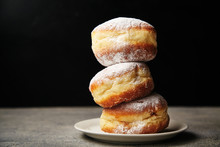 A Stack Of Three Sufganiyot Donuts With Jelly On Black Background