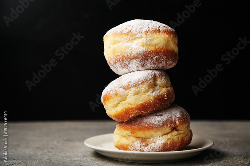 A stack of three sufganiyot donuts with jelly on black background Wallpaper Mural