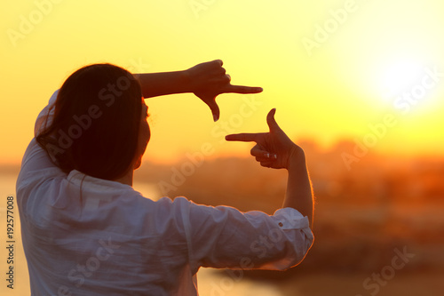 Tuinposter Zwavel geel Woman framing with fingers at sunset