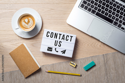 Fotografía Contact us writing in lightbox lying on desk as flatlay
