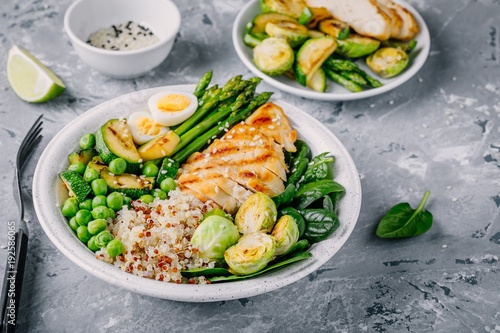 Papiers peints Assortiment Healthy grilled vegetables buddha bowl with chicken and quinoa, spinach, egg, zucchini, asparagus, Brussels sprouts and green peas