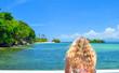 Bonde Frau mit langen Haaren steht im Bikini mit dem Rücken zur Kamera vor dem türkisenen Meer, im Hintergrund eine tropische Insel mit weißem Sandstrand