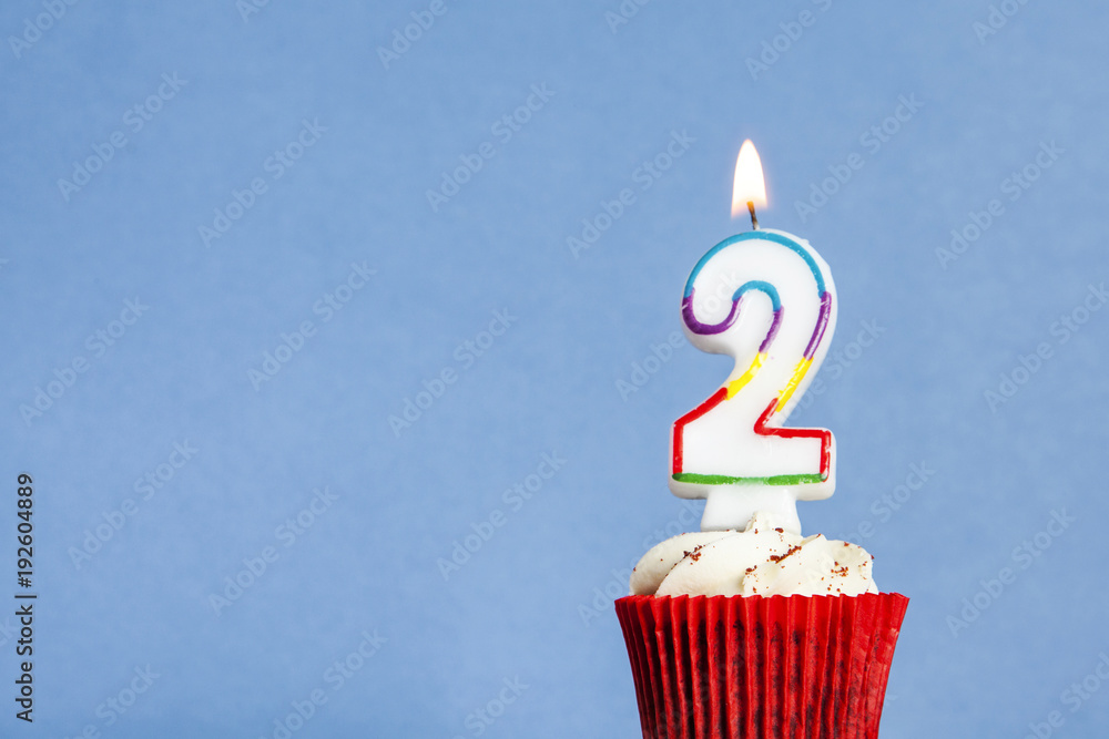 Fototapeta Number 2 birthday candle in a cupcake against a blue background