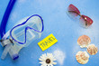 Blue background with diving mask and pink sunglasses decorated with seashells, white flower and travel card. Travelling concept